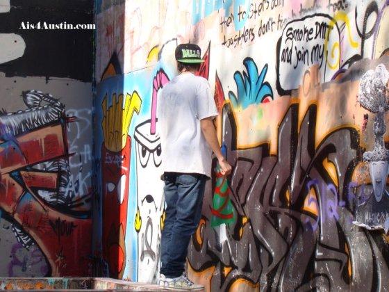artist at work at Castle Hill Graffiti Park Austin